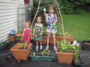 """Kids' Garden Club on 6/18, when the girls planted some herb seeds and our plants donated by Leisuretime Greenhouses. They're standing in the """"bean teepee"""" set up for the pots of beans and cucumbers to grow up and cover."""
